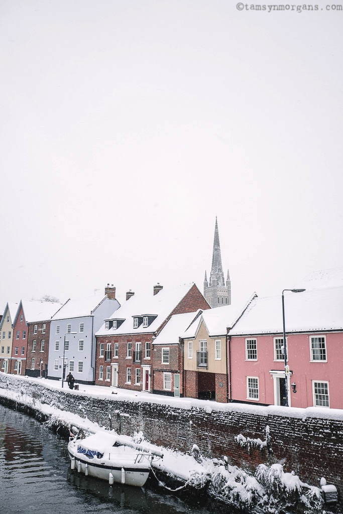 A pretty row of pastel houses with the Norwich Cathedral spire